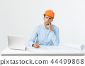 Confident smiling architect in formal wear thinking and working with blueprint papers and drawings 44499868