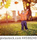 Child standing with umbrella in beautiful autumnal day 44500240