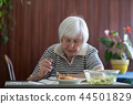 Solitary senior woman eating her lunch at retirement home. 44501829