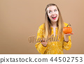 Young woman holding a thankful block and a pumpkin 44502753