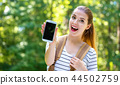 Young woman holding out a smartphone 44502759