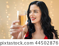 Young woman holding a champagne flute 44502876