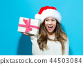 Young woman holding a Christmas gift 44503084
