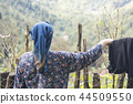 Back view of an elderly woman in front of hedge 44509550