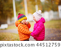 children throwing leaves in beautiful autumnal day 44512759