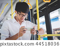 Young Asian man traveler standing on a bus using smartphone watc 44518036