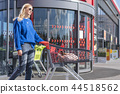woman with trolley at the supermarket door 44518562