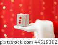 Santa holding a small Christmas gift 44519302