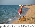 girl playing with a dog on the beach 44521522