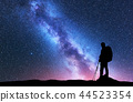Man with backpack and trekking poles and Milky Way 44523354