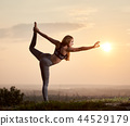 Attractive slim young woman doing yoga exercises outdoors on copy space background of beautiful sky. 44529179