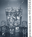 Pouring ice cube into drink glass of water. 44530583