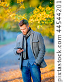 man with mobile phone in autumn season alley.  44544201