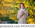 girl with mobile phone on autumn season street  44544209