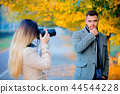 Young photographer with camera  and model  44544228