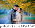young couple in autumn season alley 44544249