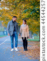 young couple in autumn season alley 44544257