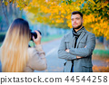 Young photographer with camera  and model  44544258