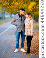 young couple in autumn season alley 44544259
