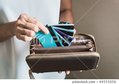 Young woman putting credit cards in her wallet 44555056