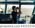 Navigational officer lookout on navigation watch looking through binoculars 44555540