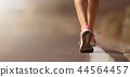 Running shoe closeup of woman running on road 44564457