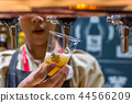 Barman or bartender pouring a beer from beer tap 44566209