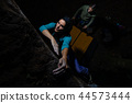 Two girls practice bouldering in the evening 44573444