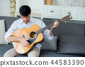 asian man relax sitting on sofa playing guitar 44583390