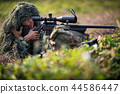 Sniper laying on the grass looking through scope. 44586447