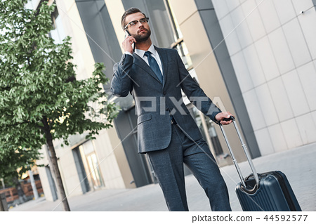 Young man with glases and suitcase calling a taxi 44592577