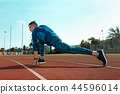 Man runner stretching legs preparing for run training on stadium tracks doing warm-up 44596014