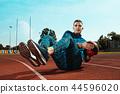 Man runner stretching legs preparing for run training on stadium tracks doing warm-up 44596020
