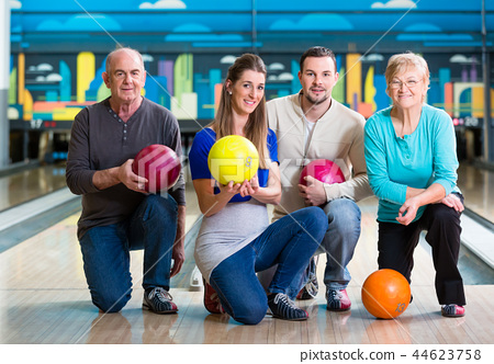 Family with multi colored bowling ball posing 44623758