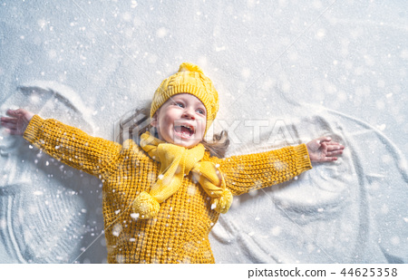 Kid making snow angel. 44625358