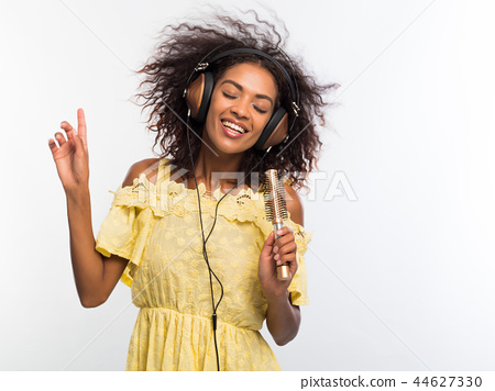 Young pretty african american woman in yellow dress singing and dancing with hair dryer instead 44627330