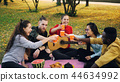 Cheerful young people multi-ethnic group are clinking glasses with drinks then drinking sitting on 44634992