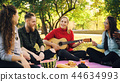 Playful young people are singing and moving hands when beautiful girl is playing the guitar during 44634993