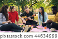 Joyful hipster is singing and playing the guitar sitting on blanket in park with friends and having 44634999