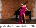 woman in fluffy dress standing near grand piano 44636707
