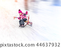Hapy cutee litlle girl having fun sledging from hill on bright sunny day. Child moving fast on 44637932