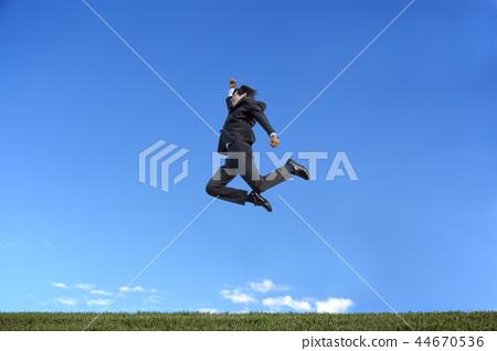 푸른 하늘을 배경으로 점프 슈트 차림의 젊은 사업가 1 명. 건강 파워 기쁨 · 도전 이미지 44670536