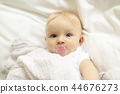 A cute baby with pacifier lying on a white bed 44676273