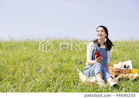 야외에서 음악을 듣고 여자 44690283