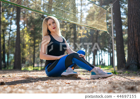Athletic girl sitting on a tennis court  44697155