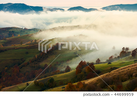 fog and rising clouds roll over the rural hills 44699959