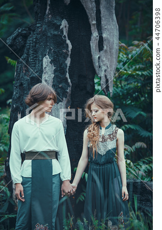 Young couple of elves outdoor agaist dying burned-down tree 44706398