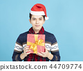 smiling young Man showing Christmas present 44709774