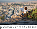 woman with a map sitting on Lycabettus Hill 44718340