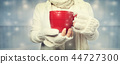 Woman holding a cup of coffee 44727300